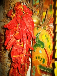 Dried peppers hang next to a painted cupboard